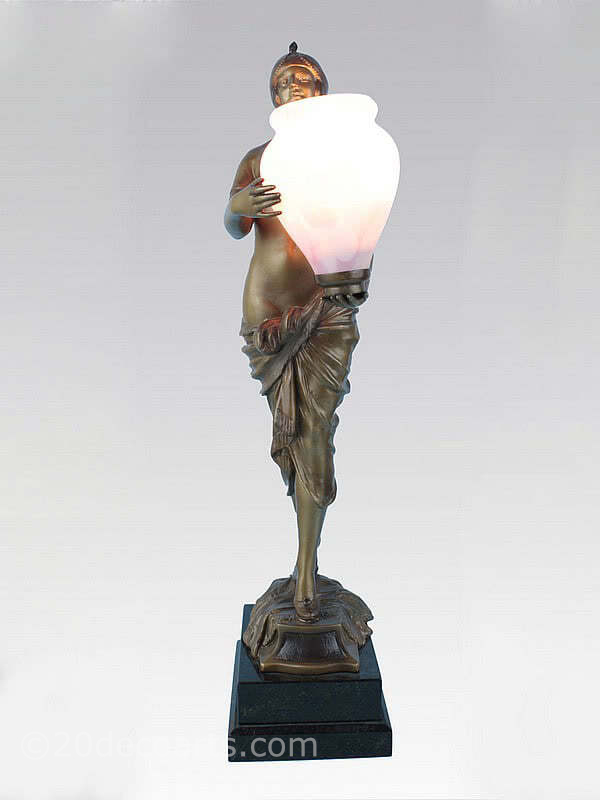 20th Century Decorative Arts | A rare art deco spelter figure lamp, circa 1930, Germany, the spelter cold-painted in shades of gold, mounted on a stepped granite base holding aloft a Czech glass urn shade