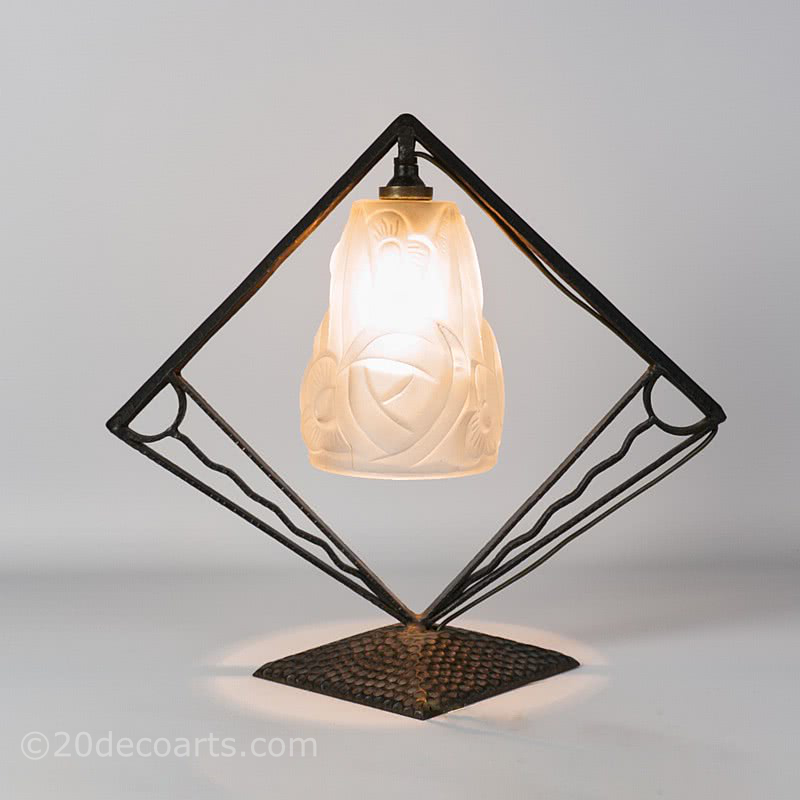 A wrought iron art deco lamp with shade by Degue, circa late 1920's, the stylised frame supporting the frosted shade