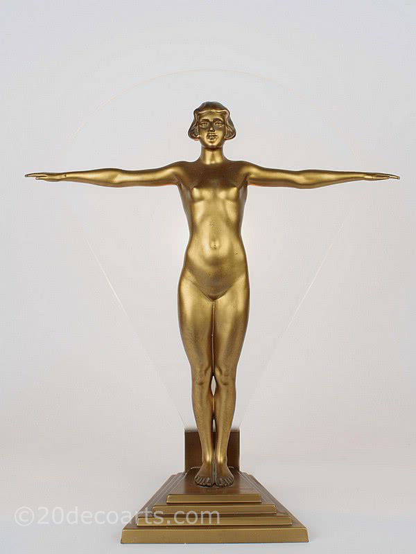 20th Century Decorative Arts |A very stylish and rare art deco figure spelter lady lamp, circa 1930, Germany, the cold-painted gold figure stood on a stepped base in front of satin finish glass