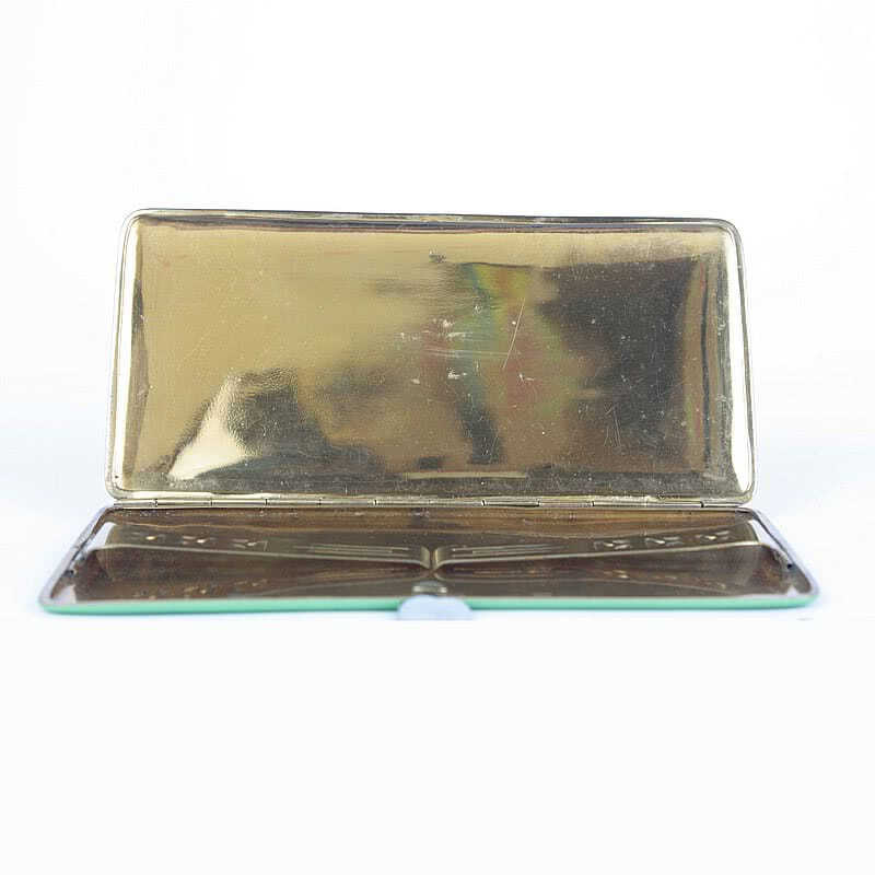 An Art Deco enamelled and gilded metal cigarette case, 1930s decorated in black and green with raised gilded lines.