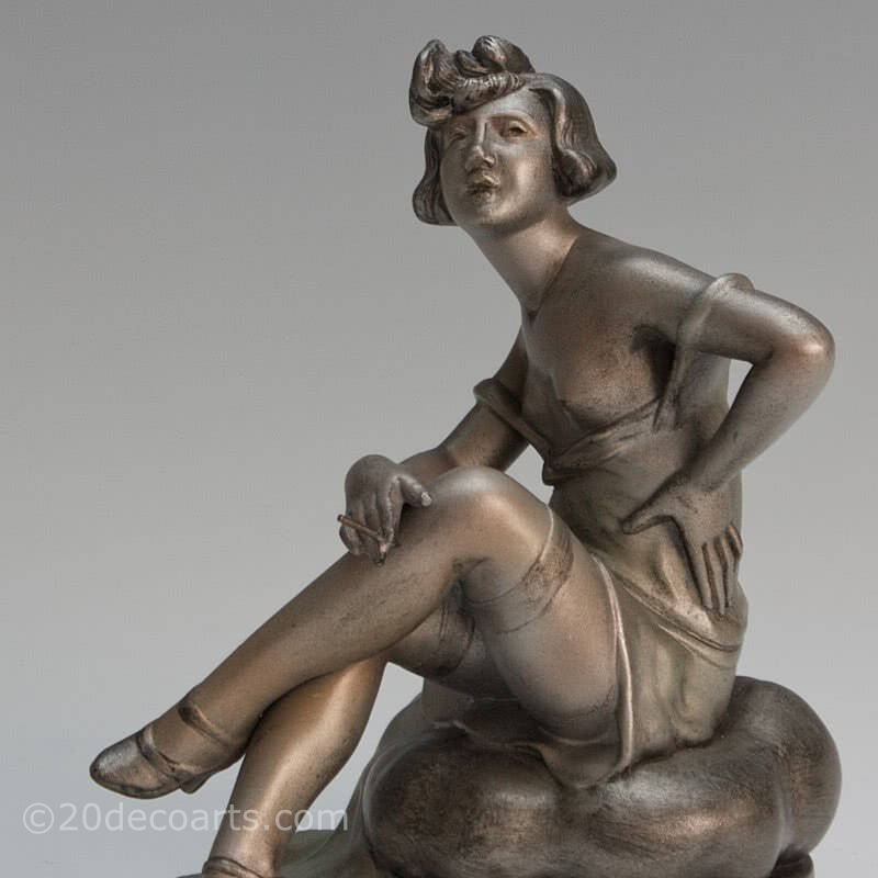 20th Century Decorative Arts |An Art Deco spelter figure by A. Lesueur France c1920s, the silvered and enamel painted young woman sat on a cushion smoking a cigarette