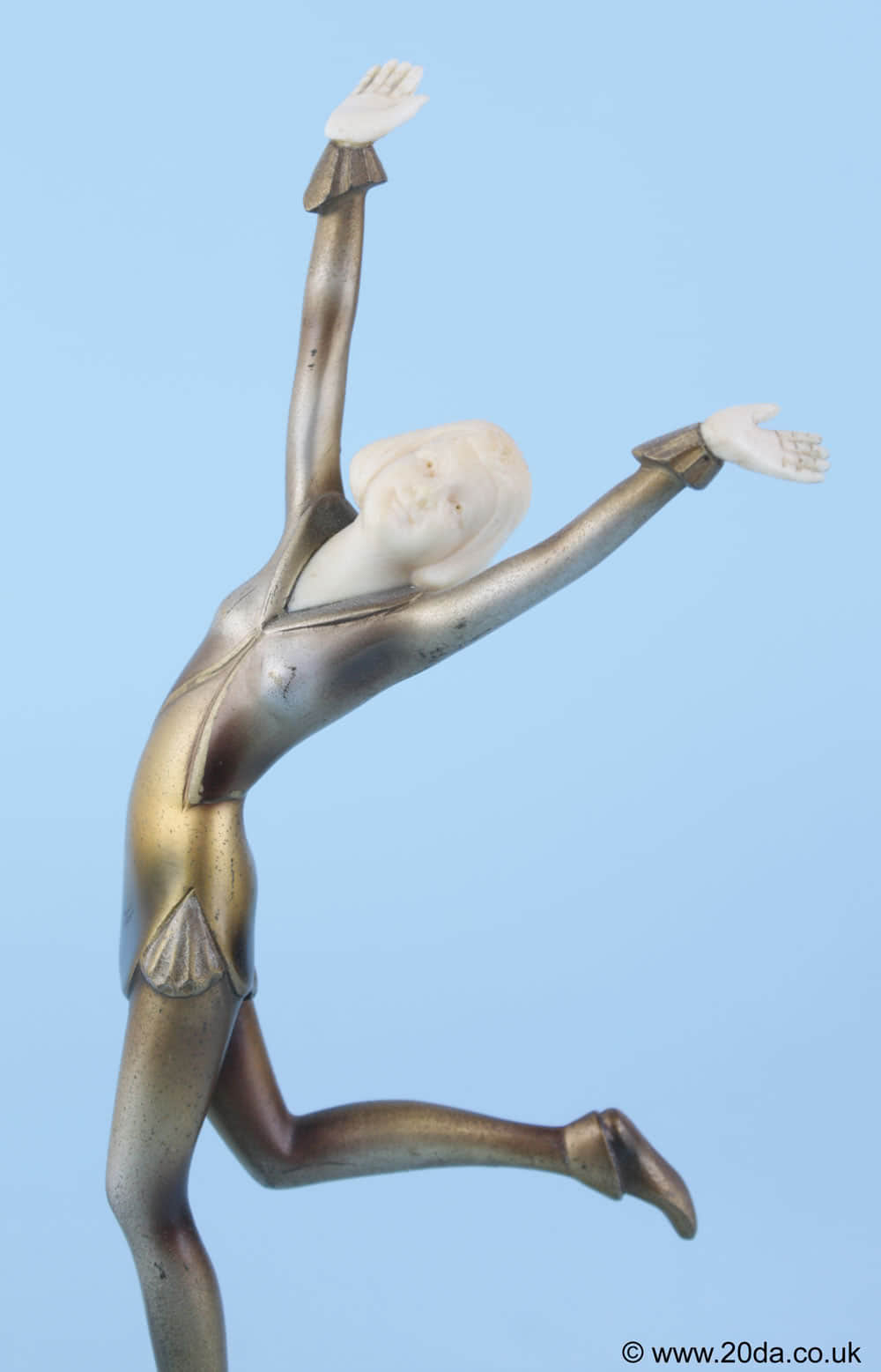 20th Century Decorative Arts |An exuberant Art Deco Austrian bronze and ivory figure by Stefan Dakon, circa 1930 depicting a stylishly attired young lady with carved ivory head and hands, and a silvered and enamelled cold-painted finish, mounted on a shaped onyx base