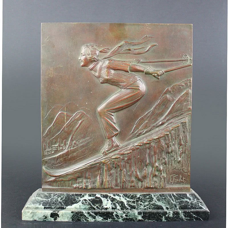 20th Century Decorative Arts |A rare Art Deco bronze sculptural plaque, circa 1930, Frederic Focht, France the patinated bronze featuring a dynamic downhill skier, mounted on a green marble base.