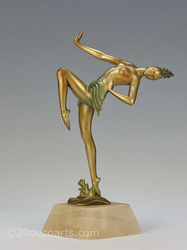 20th Century Decorative Arts |A very stylish Art Deco German spelter figure circa 1930, the female dancer in futuristic ballet costume, cold-painted gold and enamelled, mounted on a shaped alabaster base