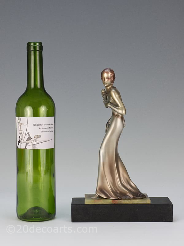 20th Century Decorative Arts | A rare Art Deco  Austrian bronze  figure by Josef Lorenzl,  circa 1930 depicting a stylish lady in evening attire with a lacquered silver and enamelled cold-painted finish, mounted on a shaped green onyx and black marble base-